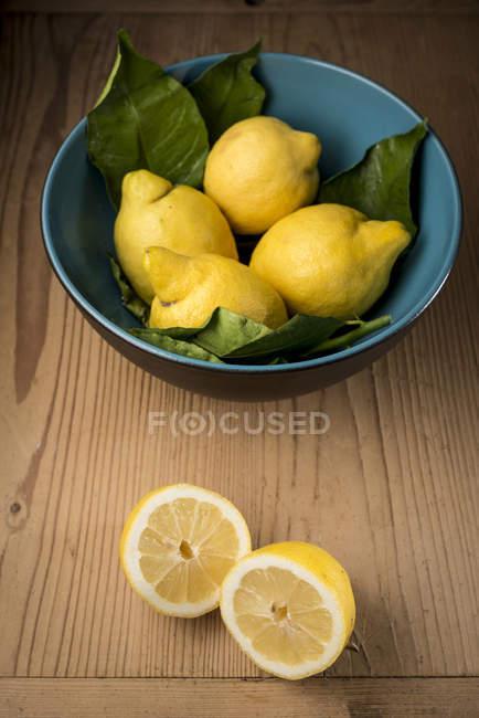 Zitronen in Schüssel auf Tisch, Stillleben — Stockfoto