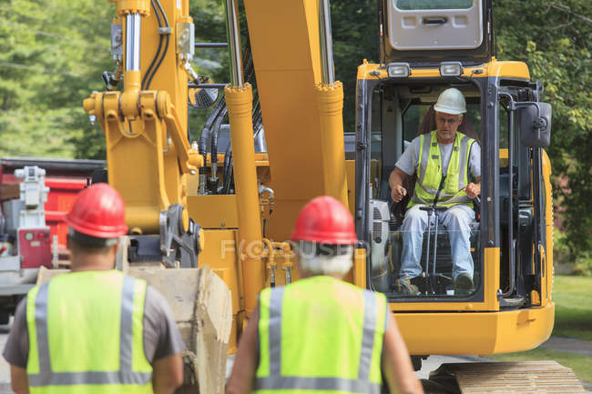 Heavy construction equipment operator in excavator with construction workers. — Stock Photo