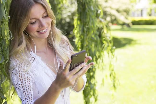 Mujer rubia mirando hacia abajo, usando smartphone y sonriendo al aire libre . - foto de stock