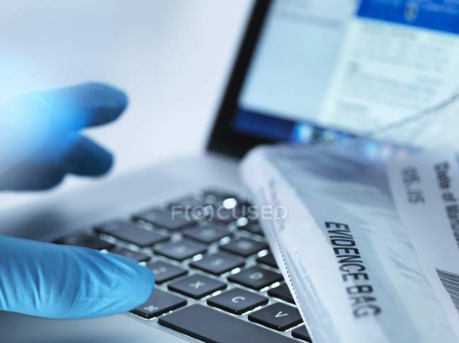 Forensic evidence lying down on laptop with reaching hand, close-up. — Stock Photo