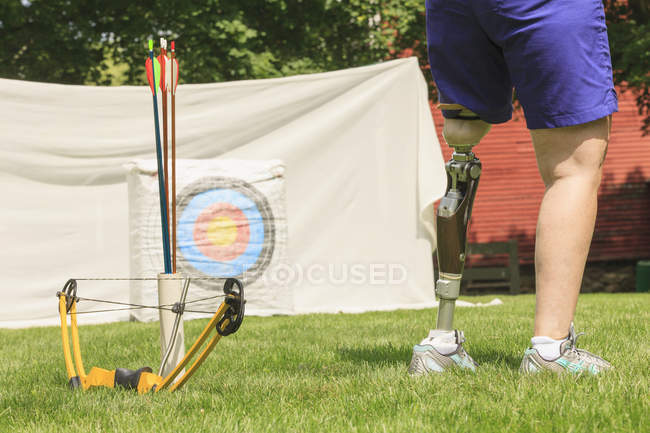 Woman with prosthetic leg preparing for archery practice. — Stock Photo