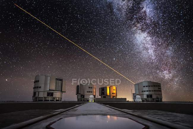 Laser beam of telescope in sky above observatory in Chile with Milky Way in background. — Stock Photo