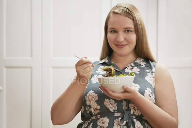 Young woman eating bowl of salad — Stock Photo