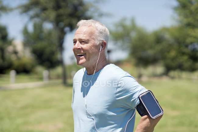 Uomo anziano che indossa smartphone su braccio e auricolari nel parco . — Foto stock
