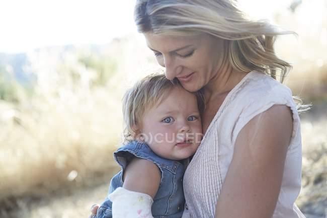 Мати дочка обійматися малюка з рукою у гіпсі. — стокове фото