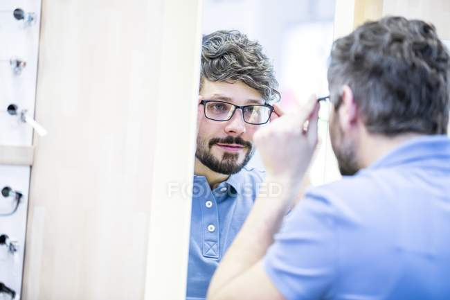 Man trying on glasses in optometrist shop. — Stock Photo