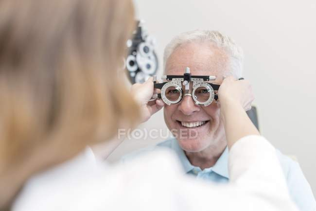 Optician testing senior man eyesight. — Stock Photo