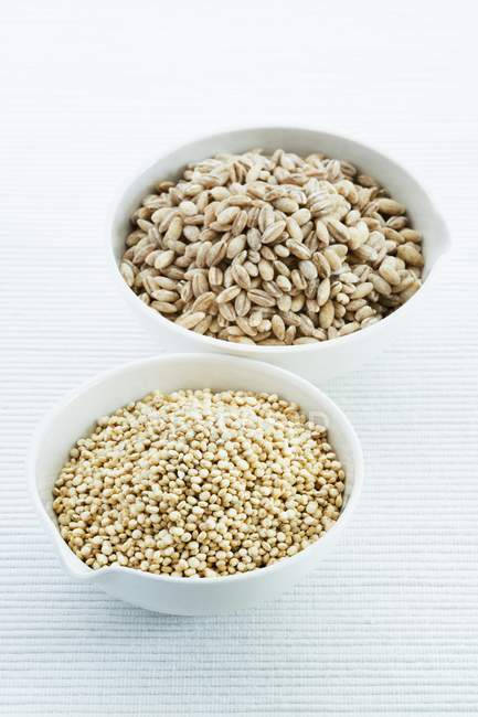Quinoa e orzo perlato in ciotole sulla tabella — Foto stock