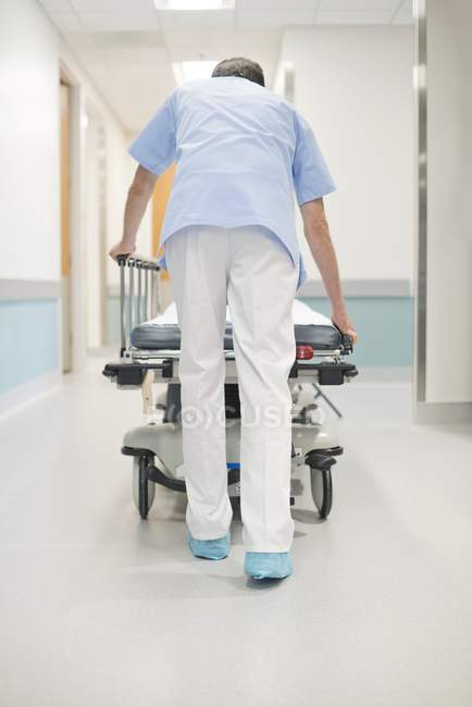 Male nurse orderly pushing bed in corridor. — Stock Photo | #161674128