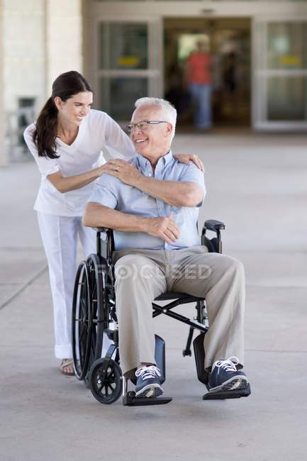 Senior man in wheelchair with healthcare worker. — Stock Photo