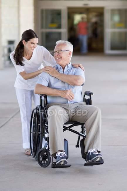 Homem idoso em cadeira de rodas com profissional de saúde . — Fotografia de Stock