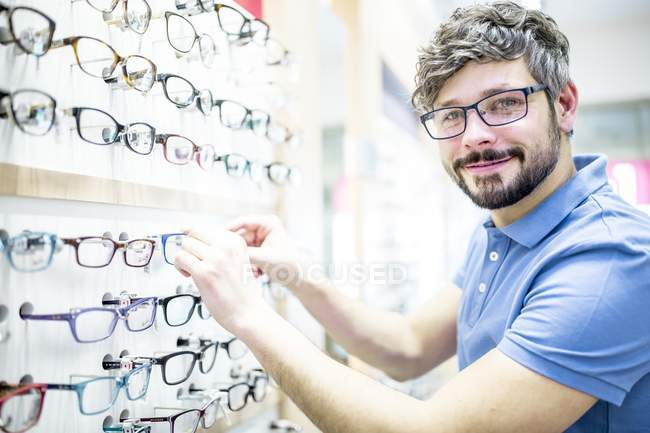 Man at glasses rack in optometrist shop. — Stock Photo