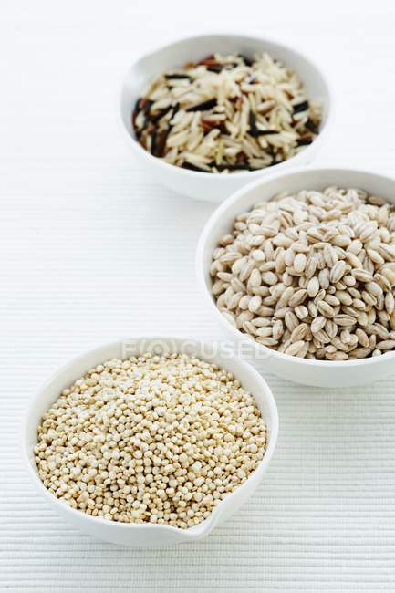Ciotole di riso, orzo perlato e quinoa. — Foto stock