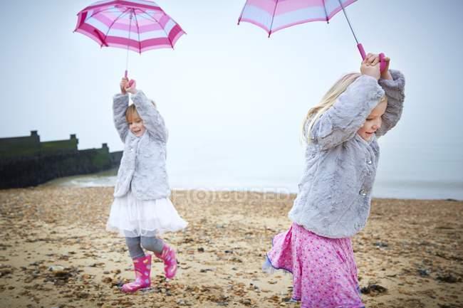 Две девушки дошкольника, ходить на пляж и проведение розовый зонтики. — стоковое фото