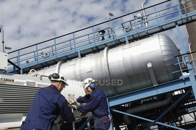 Industrial workers on oil and gas refinery with storage tanks. — Stock Photo