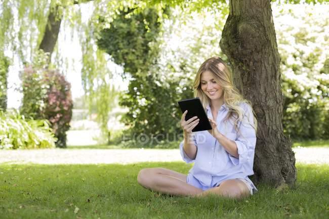 Mulher sentada debaixo da árvore e usando comprimido digital . — Fotografia de Stock