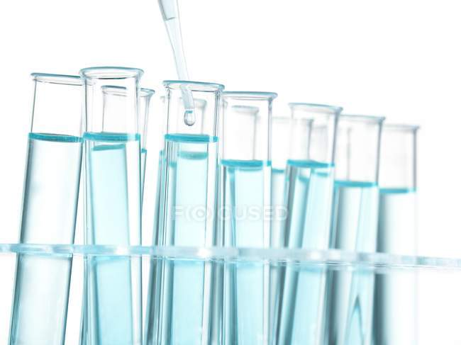 Pipette dripping liquid into test tubes. — Stock Photo