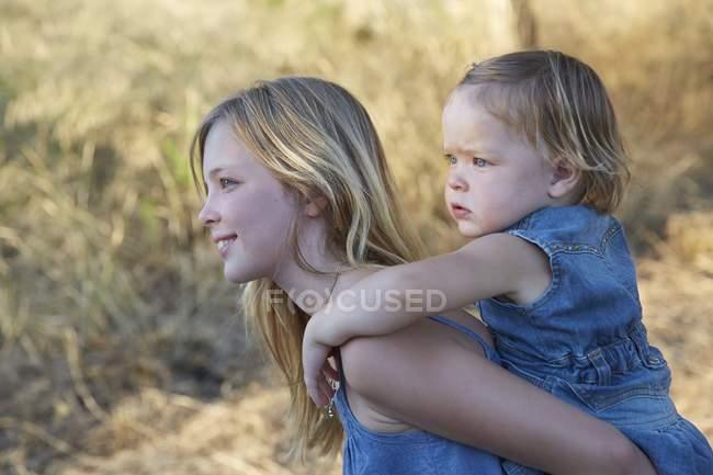Елементарний віці дівчина несучи малюк сестра на спині. — стокове фото