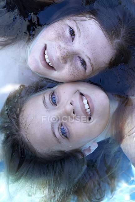 Ritratto di due ragazze in età elementare galleggianti in acqua, vista ad alto angolo . — Foto stock