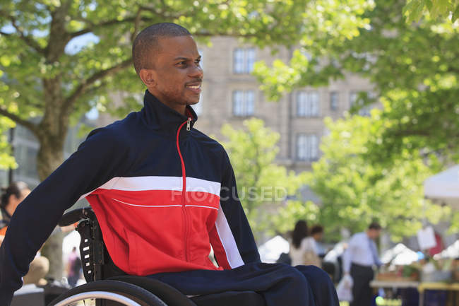 Man in wheelchair moving in the city — Stock Photo