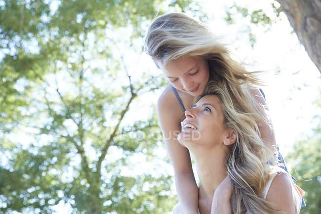Preteen girl hugging mother from behind in park. — Stock Photo