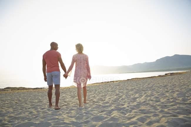 Couple tenant la main tout en marchant sur la plage . — Photo de stock