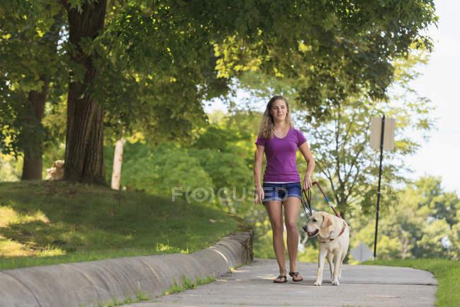 Donna con disabilità visiva che cammina con il cane di servizio . — Foto stock