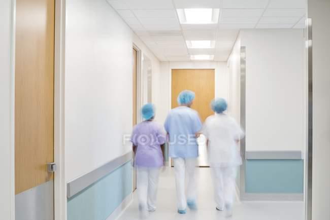 Personale medico a piedi nel corridoio dell'ospedale, vista posteriore. — Foto stock
