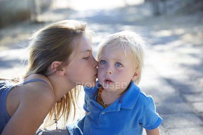Elementary age girl kissing toddler brother on cheek. — Stock Photo