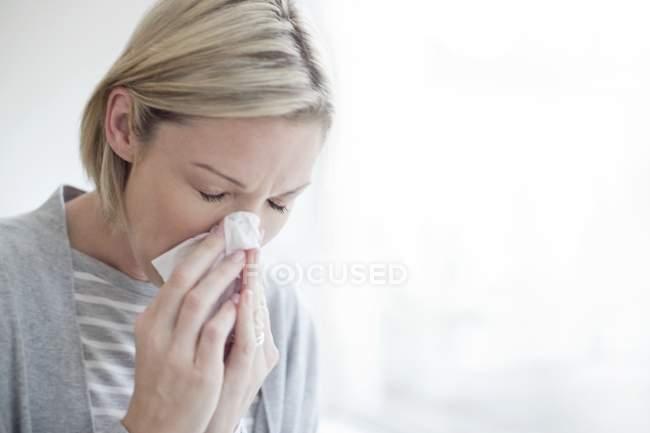 Metà di donna bionda adulta che soffia il naso nel tessuto — Foto stock