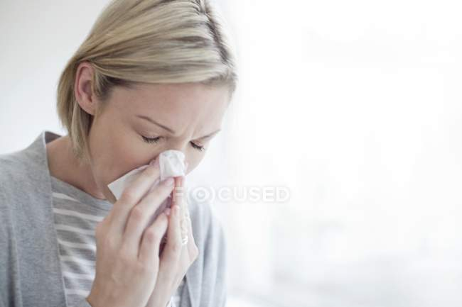 Mid adult blonde woman blowing nose in tissue. — Stock Photo