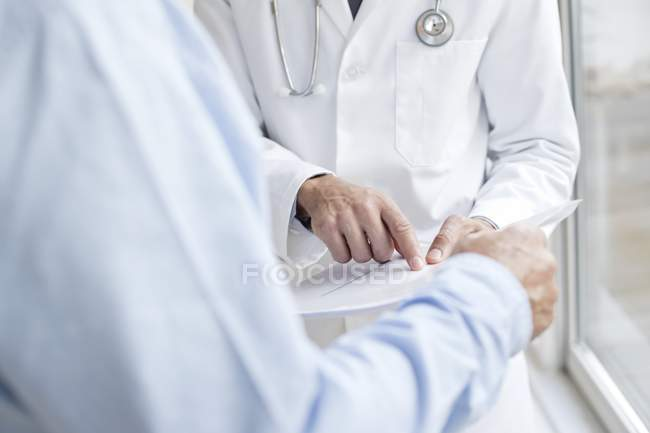Male doctor pointing at medical notes with patient. — Stock Photo