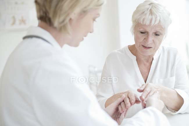 Жінці – лікарю вивчення старший пацієнта руки. — стокове фото
