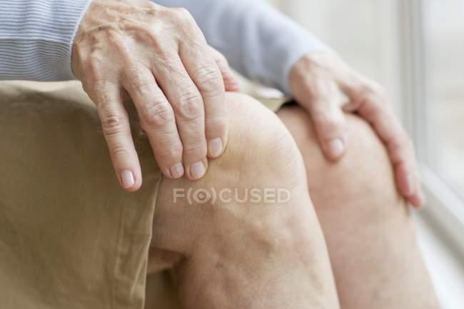 Haute femme touchant les genoux, gros plan — Photo de stock