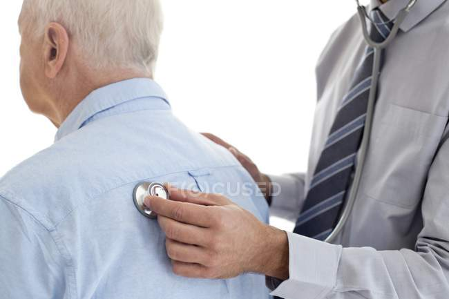 Male doctor examining senior patient, rear view. — Stock Photo