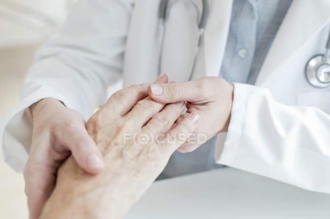 Female doctor holding senior patient hand. — Stock Photo