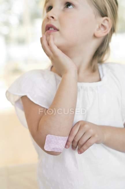 Garota de idade elementar com gesso no cotovelo. — Fotografia de Stock