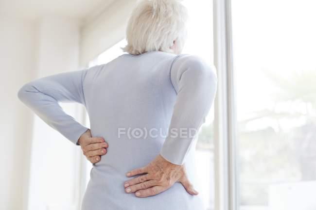 Seniorin reibt sich schmerzenden Rücken, Rückansicht. — Stockfoto