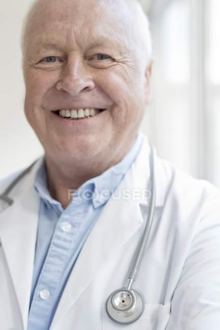Старші чоловіки лікар посміхається й дивиться в камеру. — стокове фото