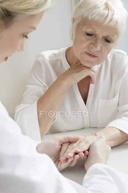 Female doctor examining senior patient hand. — Stock Photo