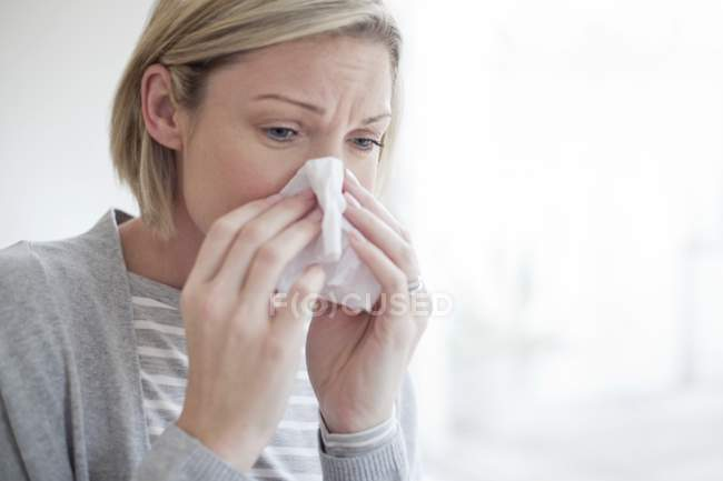 Mid adult woman blowing nose with tissue. — Stock Photo