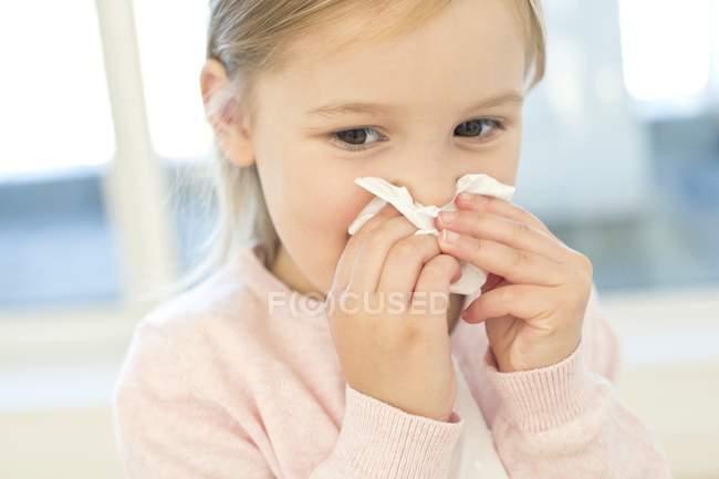 Ragazza di età scolare che pulisce il naso nel tessuto — Foto stock