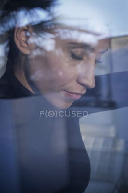 Mid adult woman day dreaming behind glass pane. — Stock Photo