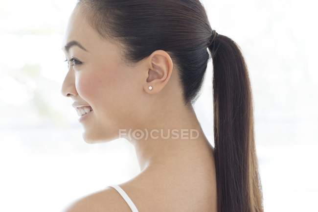 young smiling woman with ponytail profile white background side