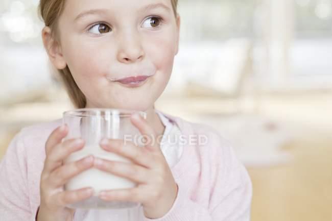 Девочка младшего возраста пьет молоко . — стоковое фото