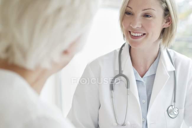 Ärztin lächelt Seniorin an. — Stockfoto