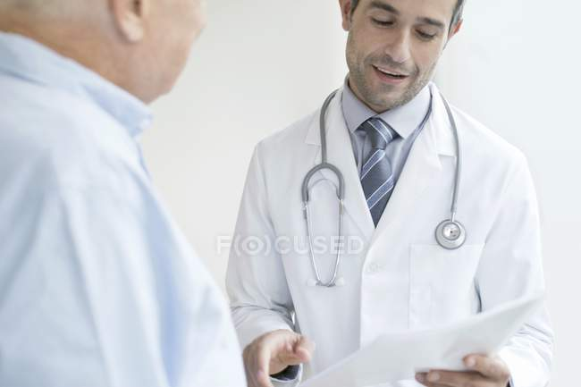 Male doctor holding medical notes and talking to senior patient. — Stock Photo