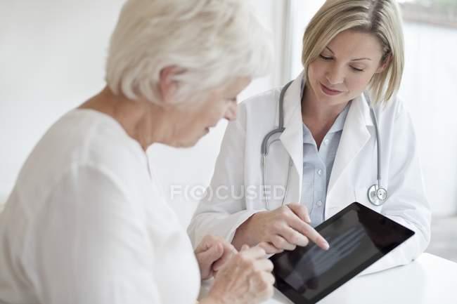 Ärztin zeigt Seniorin Röntgenbild der Hand auf digitalem Tablet. — Stockfoto