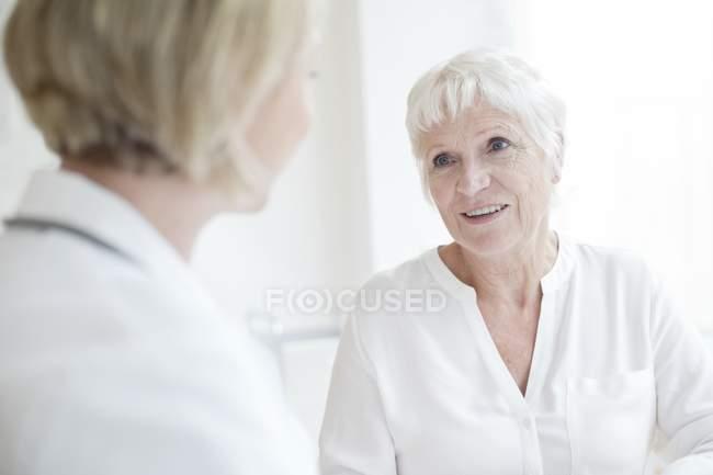 Seniorin hört Ärztin zu. — Stockfoto