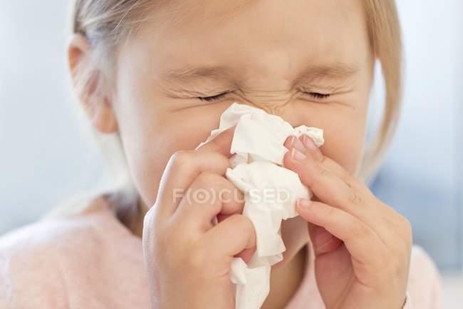 Elementary age girl sneezing into tissue. — Stock Photo